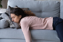 Tired Unmotivated Young Woman Falls Asleep On Cozy Couch Indoors, Having No Energy After Hard Working Day. Exhausted Caucasian Lady Napping On Comfortable Sofa In Living Room, Fatigue Concept.