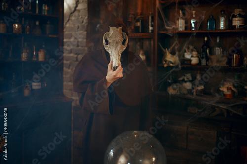 Photographie Male exorcist in black hood holds animal skull