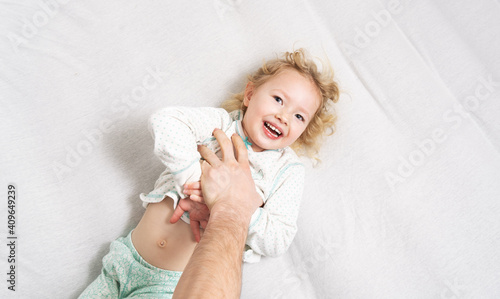 Fotografia Family time: a little girl lies on the bed and laughs cheerfully because of the tickling of her father