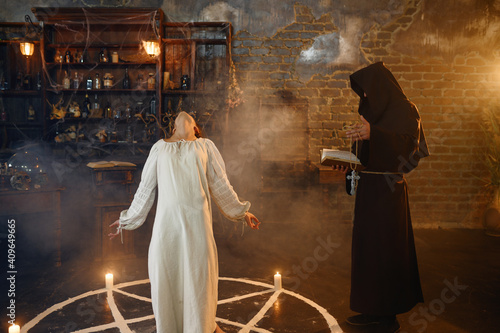 Exorcist in hood casting out demons from a woman Fototapet
