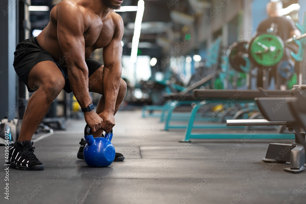 Fototapeta Cropped of black muscular man working out with kettlebell