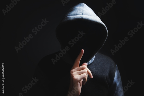 Fototapeta hooded man making silence gesture