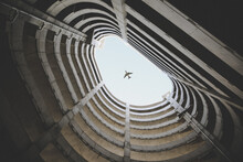 Bottom View Photo Of Airplane Passing In The Middle Of A Building