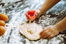 Close Up Of Kid Hands Carving Dough With Cookie Cutters. Easter Baking Preparation. Cookies For Christmas.