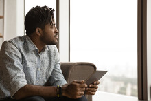 Thoughtful Pensive African Man Sit On Sofa Distracted From Modern Pad Decide Whether To Use Good Proposal. Dreamful Black Male Look At Window Ponder On Interesting News On Gadget Screen. Copy Space