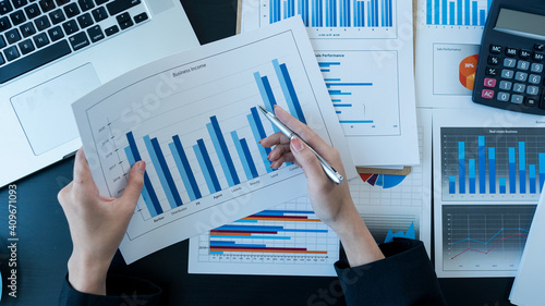 Photo The graph in the hand of a business woman analyzes the graph on the desk where a