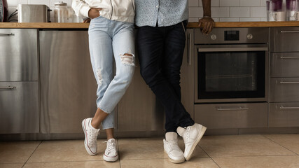 Young black couple in stylish casual clothing posing at home crossing legs in trendy sport shoes. Close up cropped view of african spouses cleaning company customers satisfied with tidy clean kitchen