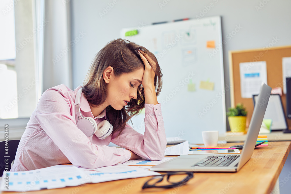 Fototapeta Tired young woman in office having headache working on project