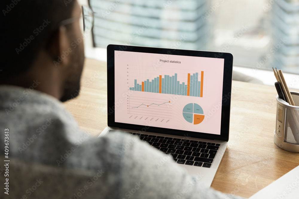 Fototapeta Black man sales manager financial analyst thinking on statistical information comparing data in charts graphs accessing marketing strategy effectiveness. Over shoulder view on laptop screen. Close up