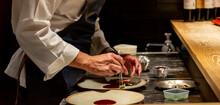 料理を盛り付けるシェフの手元