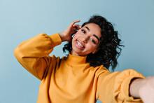 Pleased Girl In Dental Braces Taking Selfie. Studio Shot Of Gorgeous Woman In Yellow Sweatshirt.