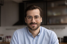 Portrait Of Young Smiling Handsome Bearded Man In Glasses Looking At Camera Chatting With Wife Friend By Videocall. Millennial Male Team Leader Organize Virtual Meeting Workshop With Employees Online