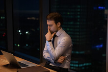Doubtful Bearded Businessman Ponder By Computer Hesitate Before Making Risky Decision. Pensive Young Man Worker Sit Before Laptop At Office Far Into Night Give Careful Thought To Information On Screen