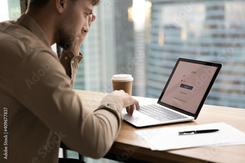 Obraz Thoughtful young man worker student sit by laptop prepare to input personal data entering social network account. Pensive millennial guy creating strong login password to electronic bank app. Close up - fototapety do salonu