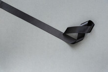Black Ribbon Showing Symbol Of Remembrance Or Mourning For Mass Grief Incident Over Grey Background With Copy Space