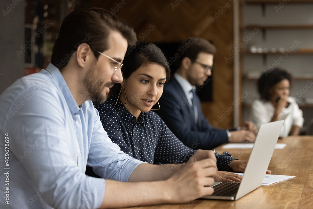 Fototapeta Focused millennial male intern look at laptop screen listen to skilled indian female mentor. Hindu woman experienced worker consult young man new employee help in computer work at corporate network
