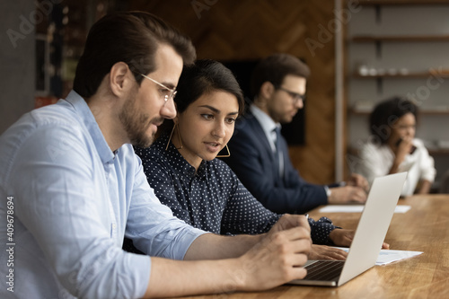 Fototapeta Focused millennial male intern look at laptop screen listen to skilled indian female mentor