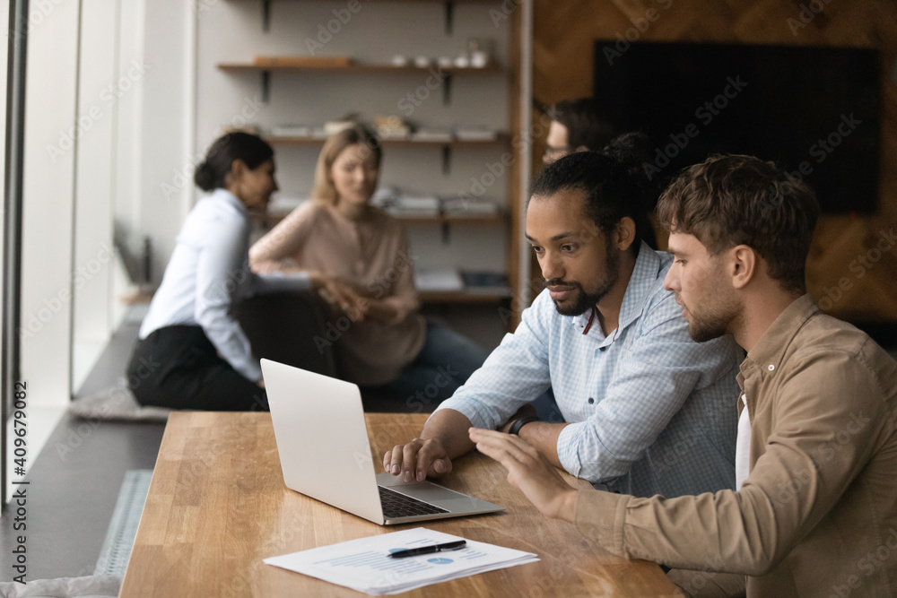 Fototapeta Two diverse male employees colleagues sit by laptop in modern office area engaged in working on project startup together. Capable young man share idea experience with black guy intern trainee using pc