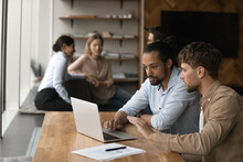 Two Diverse Male Employees Colleagues Sit By Laptop In Modern Office Area Engaged In Working On Project Startup Together. Capable Young Man Share Idea Experience With Black Guy Intern Trainee Using Pc