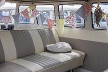 The Interior Of A Camper Van With Leather Seating And Bunting