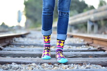 Person In Blue Denim Jeans And Multi Color Socks Standing On Brown Wooden Pathway