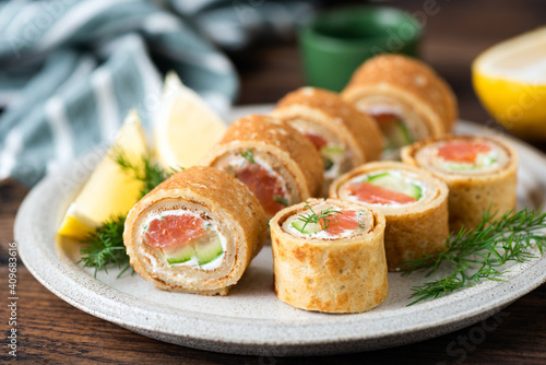 Valokuva Crepe rolls with salmon and cream cheese on a plate