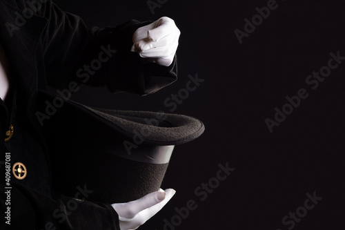 Hand gestures. Showman shows disappearing tricks in a hat, white gloves and black top hat, black background
