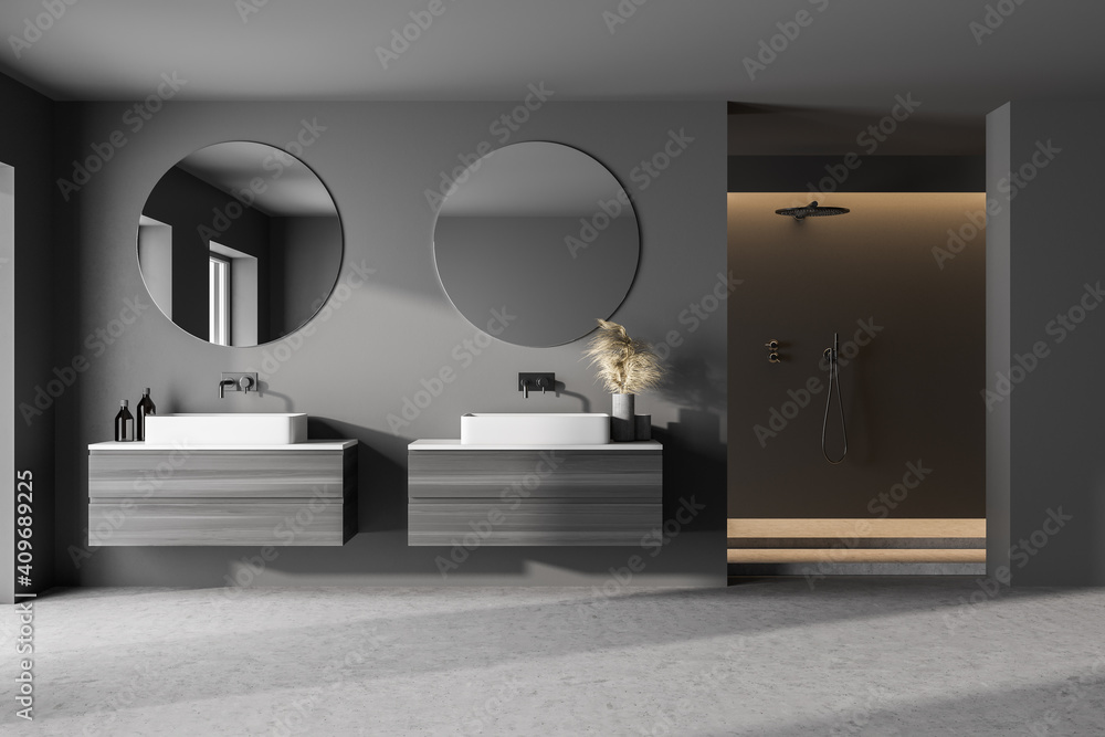 Fototapeta Interior of modern bathroom with dark gray and tiled walls, concrete dark floor, sink with round mirror and cabinets and shower stall. Concept of spa. 3d rendering