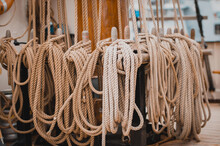 Closeup Of Thick Ropes On A Wooden Stand Of A Ship Captured During The Daytime
