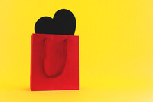 Black Heart Shape In Red Packaging On Yellow Background, Gift For Valentine's Day. Selective Focus