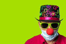 Man In Corona Und Covid 19 Times At Carnival With Red Clown Nose, Sun Glasses And Yellow Background, Copy Space