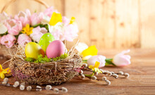 Easter Composition With Easter Eggs In Nest, Spring Flowers And Branches Of Pussy Willows.