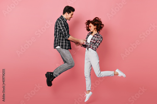 Full length shot of couple jumping and holding hands. Young people celebrating anniversary isolated on pink.