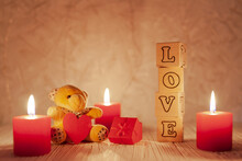 From Wooden Cubes With Letters Laid Out The Word Love, Next To There Are Three Red Burning Candles, A Baby Bear With A Red Heart