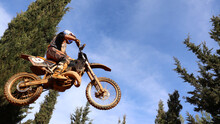 Professional Dirt Bike Motocross Rider Performing Stunts And Flying From Jump In Extreme Terrain Track