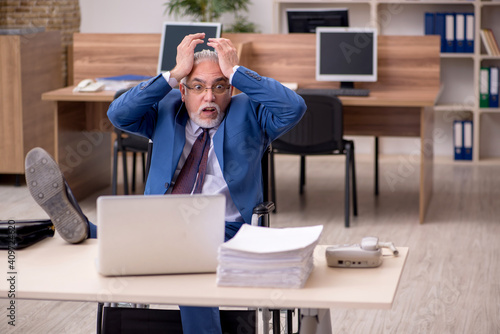 Old businessman employee in wheel-chair working in the office