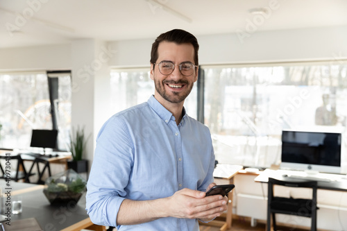 Obraz Happy business leader wearing glasses, holding cellphone, looking at camera. Portrait of businessman posing in office, satisfied with using online app on mobile phone, Communication concept - fototapety do salonu