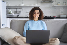 Happy Hispanic Teen Girl Holding Laptop Computer Device Technology Sitting On Couch At Home. Smiling Young Woman Using Apps, Searching Online, E Learning, Studying Browsing Internet On Sofa.