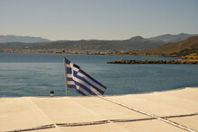 The Flag Of Greece With The Coast Of Crete In The Background.