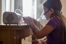 A Little Girl In A Mask Does Home Injections And Plays A Mobile Game So As Not To Get Bored.