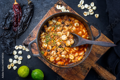 Traditional slow cooked Mexican pozole rojo soup with ground minced beef, hominy maiz and dry ancho paprika offered as top view in cast-iron roasting dish on old rustic wooden board