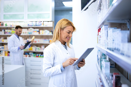 Fotomural Beautiful blonde pharmacist typing on tablet computer and selling medicine online in drugstore