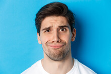 Head Shot Of Skeptical And Disappointed Man, Grimacing Complicated, Standing Against Blue Background