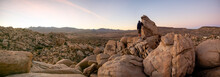 Panorama Of Man Hiking Among Field Of Boulders At Dusk With Sunset Sky  Yucca Valley, California Near Joshua Tree National Park On A Sunny January Day With Dramatic Sky