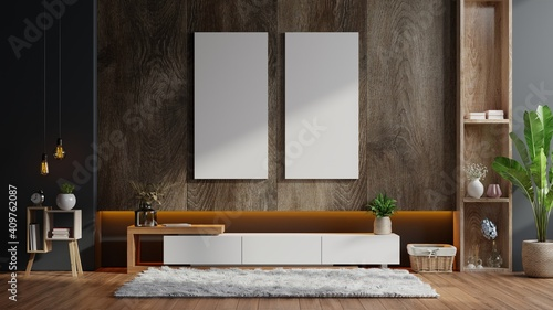 Fototapeta Poster mockup with vertical frames on empty dark wooden wall in living room interior with cabinet