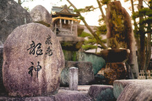 Stone With Kanjis And Little Wooden Altar At Buddhist Temple In Miyajima At Sunset, Japan