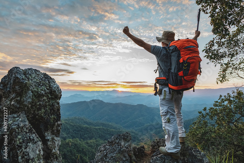 Obraz Hiker with backpack standing on top mountain sunset background. Hiker man hiking living healthy active lifestyle. - fototapety do salonu