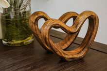 Two Handmade Wooden Carved Hearts On A Table. Couple Relationship Valentine Day Concept
