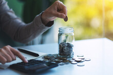 Closeup Image Of A Woman Putting Coins In A Glass Jar And Calculating On Calculator For Saving Money And Financial Concept