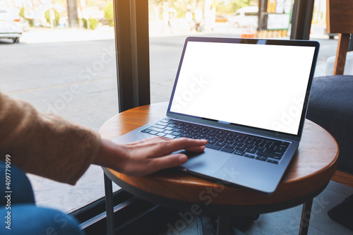 Obraz Mockup image of a woman using and touching on laptop touchpad with blank white desktop screen - fototapety do salonu